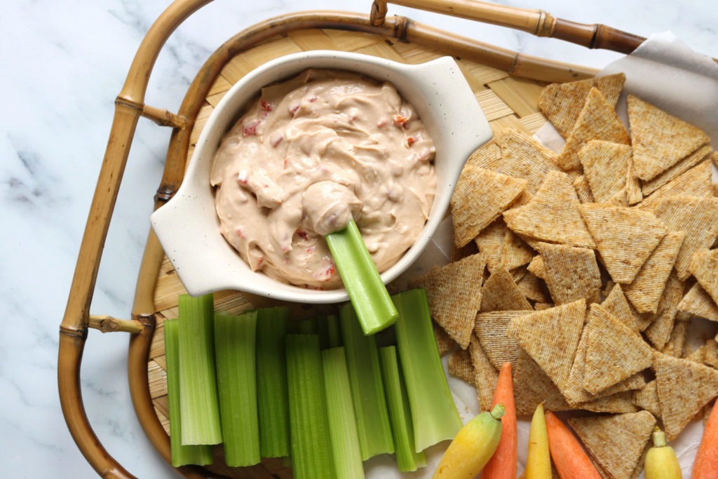 vegan pimento cheese dip on a serving tray surrounded by carrots, celery, and chips