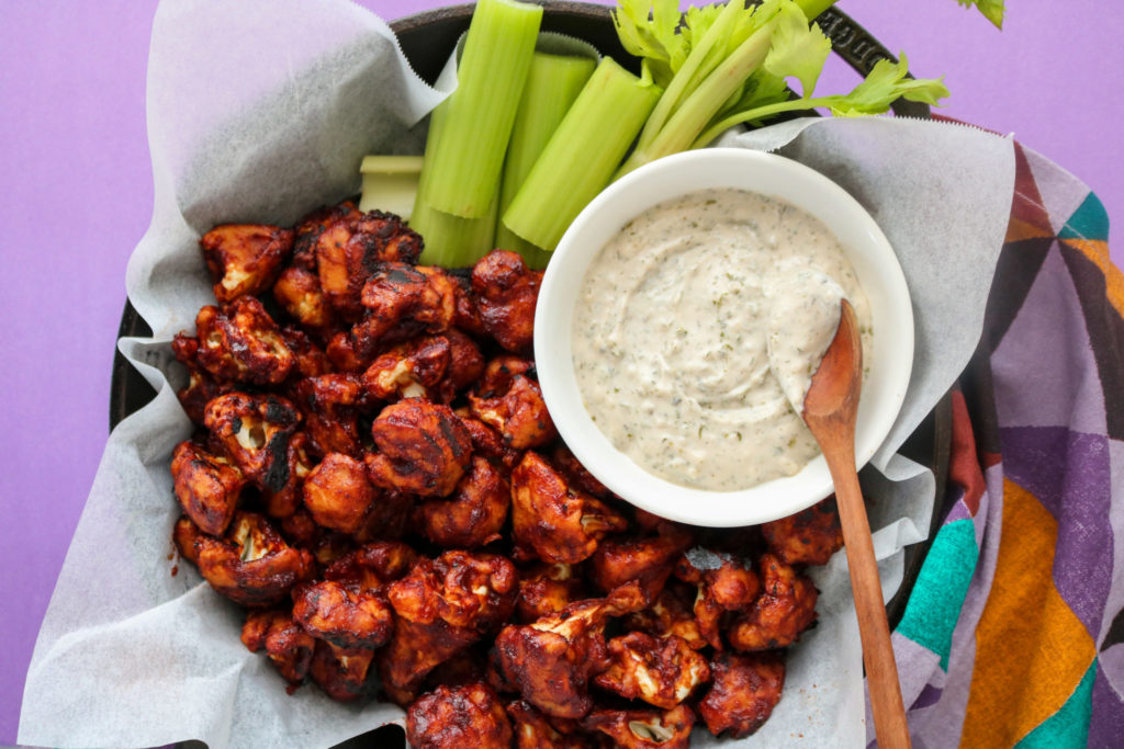BBQ cauliflower wings with vegan ranch dip in a bowl and celery