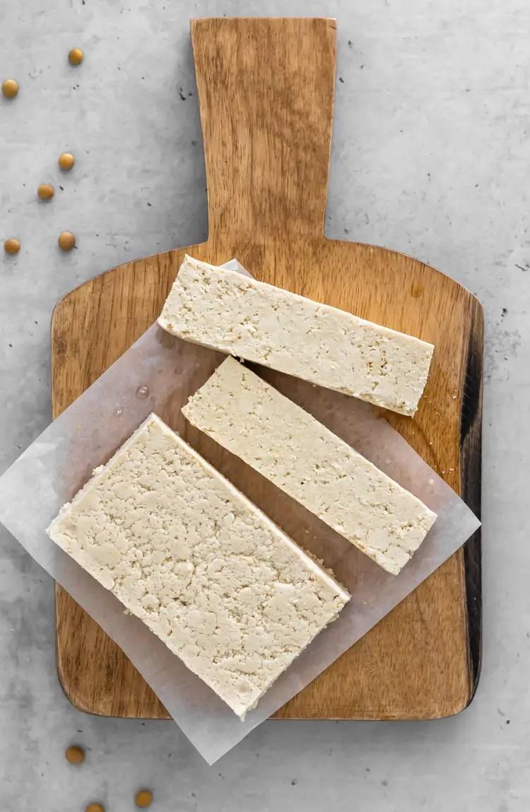 tofu caseiro fatiado em uma tábua de maneira
