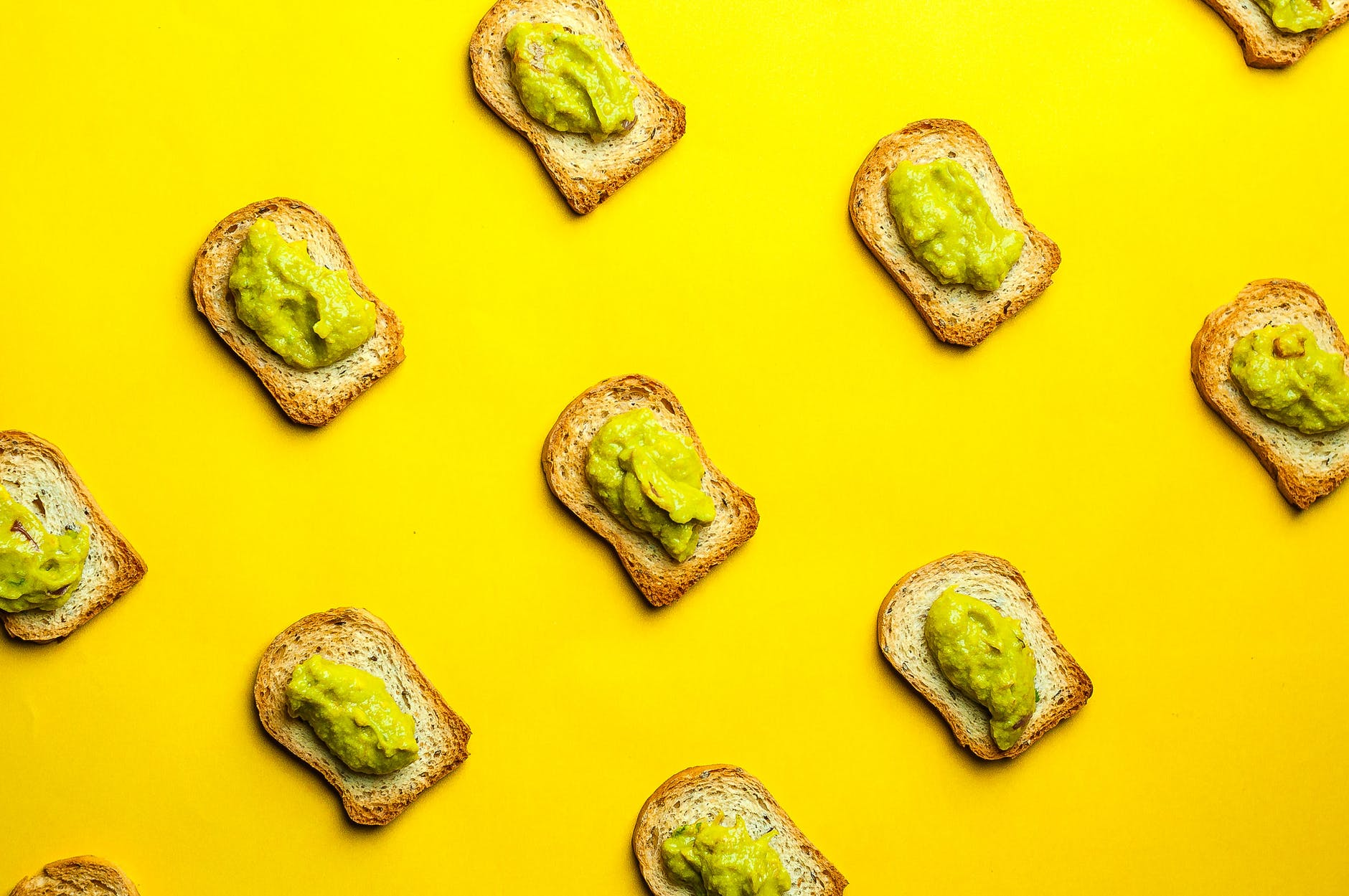 toasts with yummy guacamole placed on yellow background