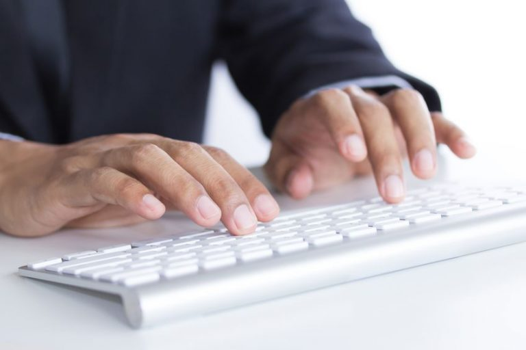 man s hands typing on keyboard selective focus