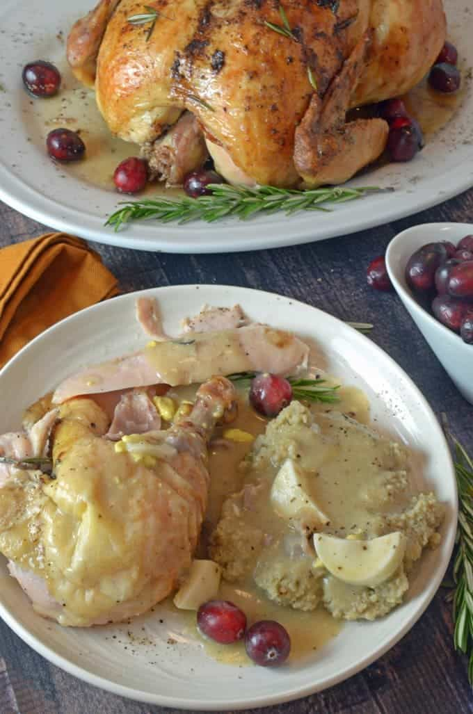 Chicken and cornbread dressing covered with giblet gravy and a roast chicken in the background.