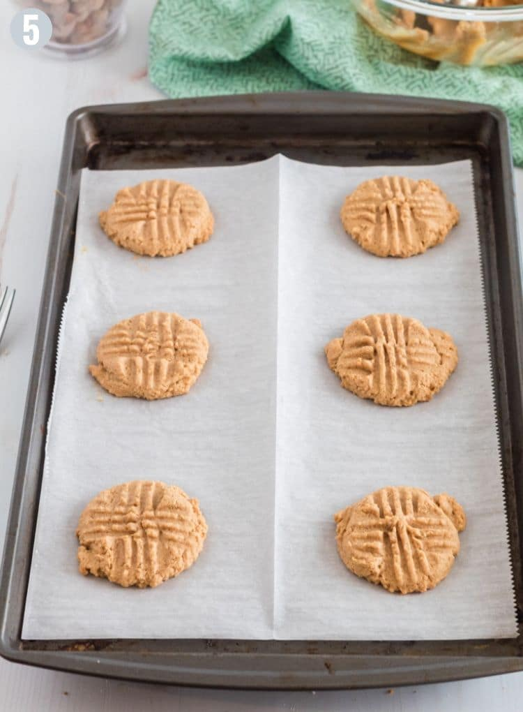 Parchement paper-lined baking sheet of freshly baked peanut butter cookies
