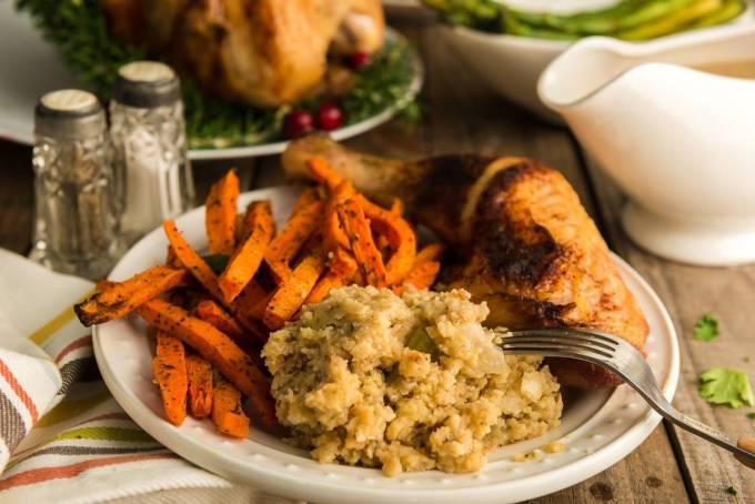 Plate of Thanksgiving dinner with homemade dressing and homemade gravy.