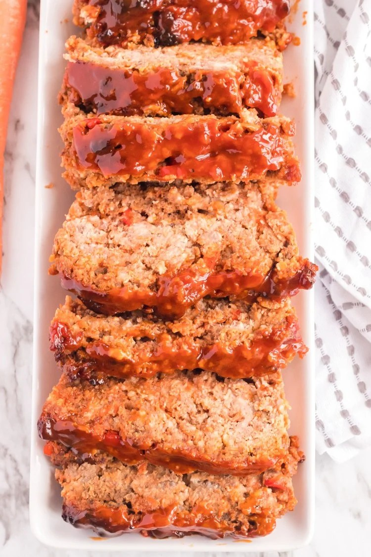 Sercing platter of whole meatloaf cut into slices.