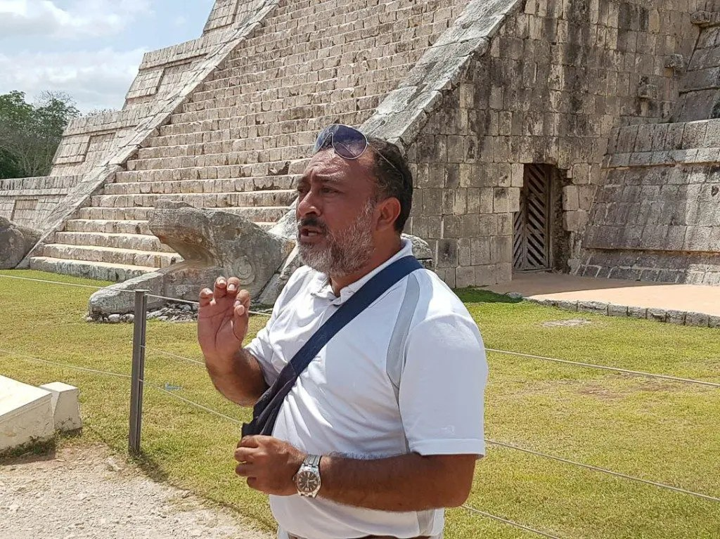 A tour guide explains the history of the Mayan people on a Chichen Itza tour