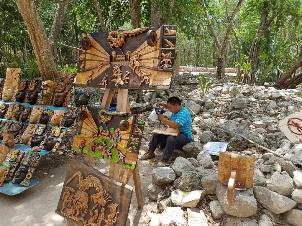 Local artist and resident Efrain Cetz carves wood at Chichen Itza