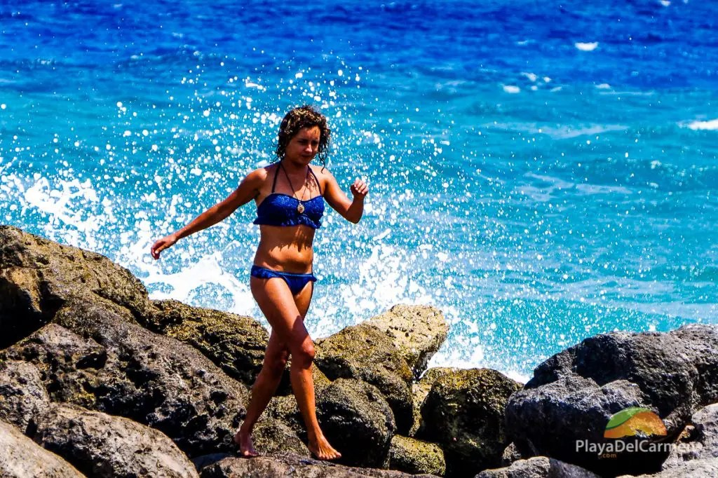 A woman walks along the rocks in Puerto Aventuras