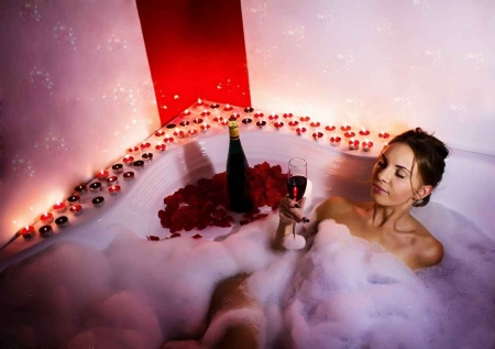A woman enjoying a large glass of wine in a candlelit Jacuzzi.