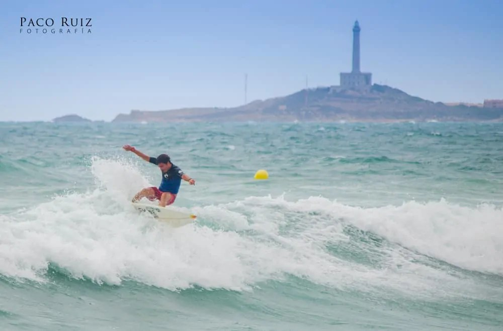 Surfer in the waters of the Cabo de Palos lighthouse