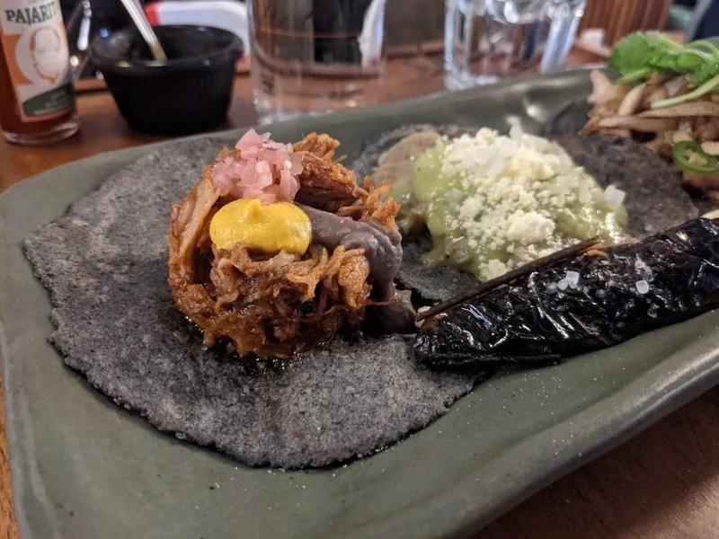 Tacos de cochinita pibil with blue corn tortillas and a fried jalapeño chile