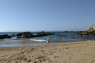 child playing in the tidepools at Conchas Chinas Beach in Puerto Vallarta