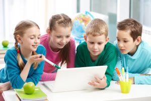 Grupo de niños mirando una computadora portatil