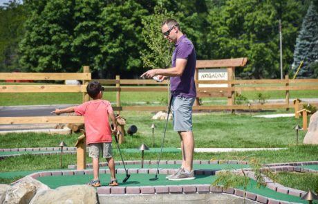 Father and son playing on a miniature golf course on a bright sunny day