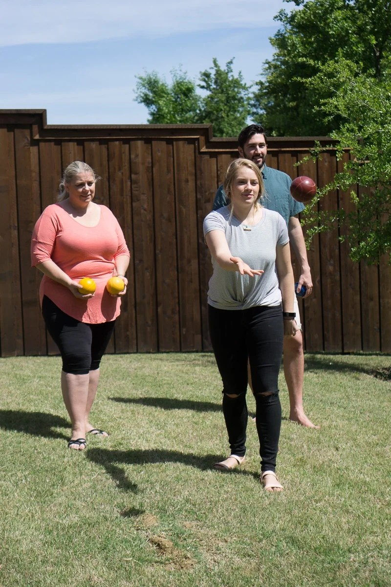 Tossing bocce balls while playing outdoor party games