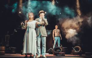 Two men and a woman on the stage of the theater