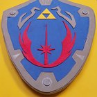 """o0V NcrGg cRF4S hld  hQDzzJlCu9cXA5VMoG wvQ My stepson is obsessed with Legend of Zelda and the Star Wars Clone Wars cartoon. He said he wanted to be """"Link Skywalker"""" for an upcoming comic con. Here is my Jedi Order Hylian shield I made for him."""