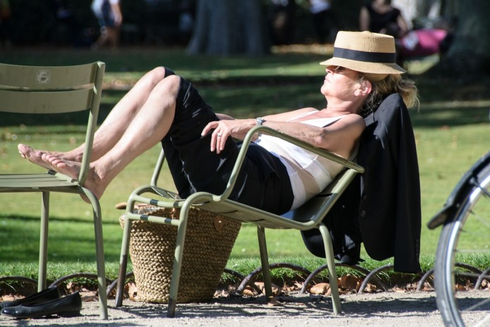 Mulher dormindo sentada ao sol
