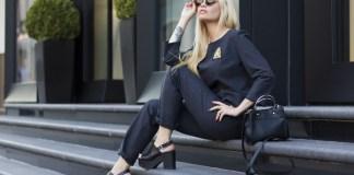 Mulher sentada na calçada de óculos escuros