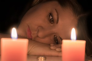 Woman sad looking at two candles. Wrongful Death