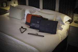 The compact and versatile range of Protégé folding garment bags on a hotel bed