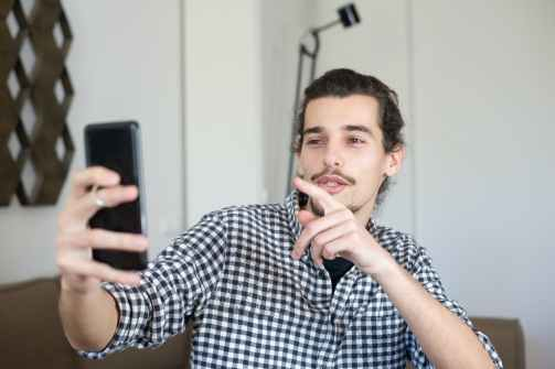 a man in checkered shirt on a video call