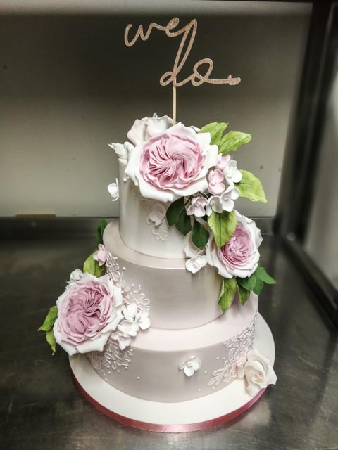 Pink ombre wedding cake with large roses, hydrangea and green foliage