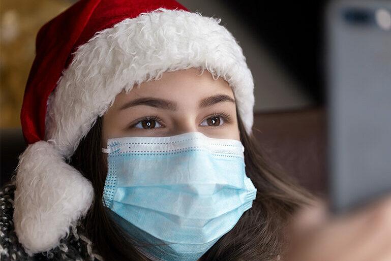 Weihnachten: Ein Mädchen mit Nasen-Mund-Maske und Nikolausmütze