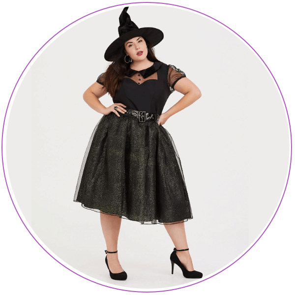 Woman wearing a witch hat, black top and black skirt
