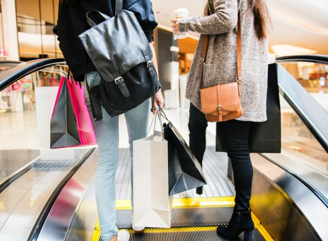 Two women with shopping bags on an escalator