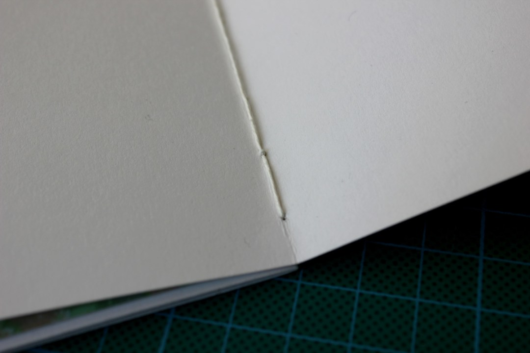 Make a loop around the long stitch in the first piece of folded paper