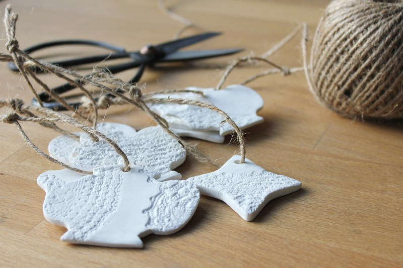 Adding a burlap twine to the paper clay Christmas ornaments as a finishing touch