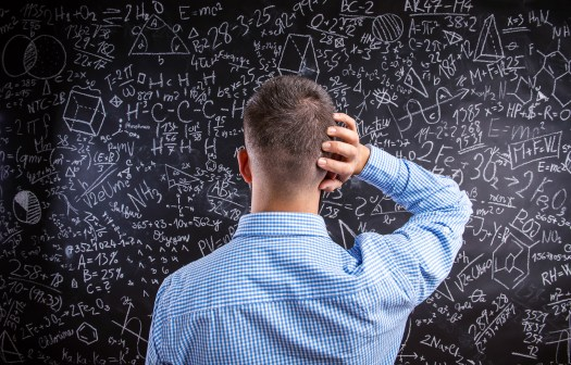Photo of confused man in front of a blackboard full of mathematical equations.