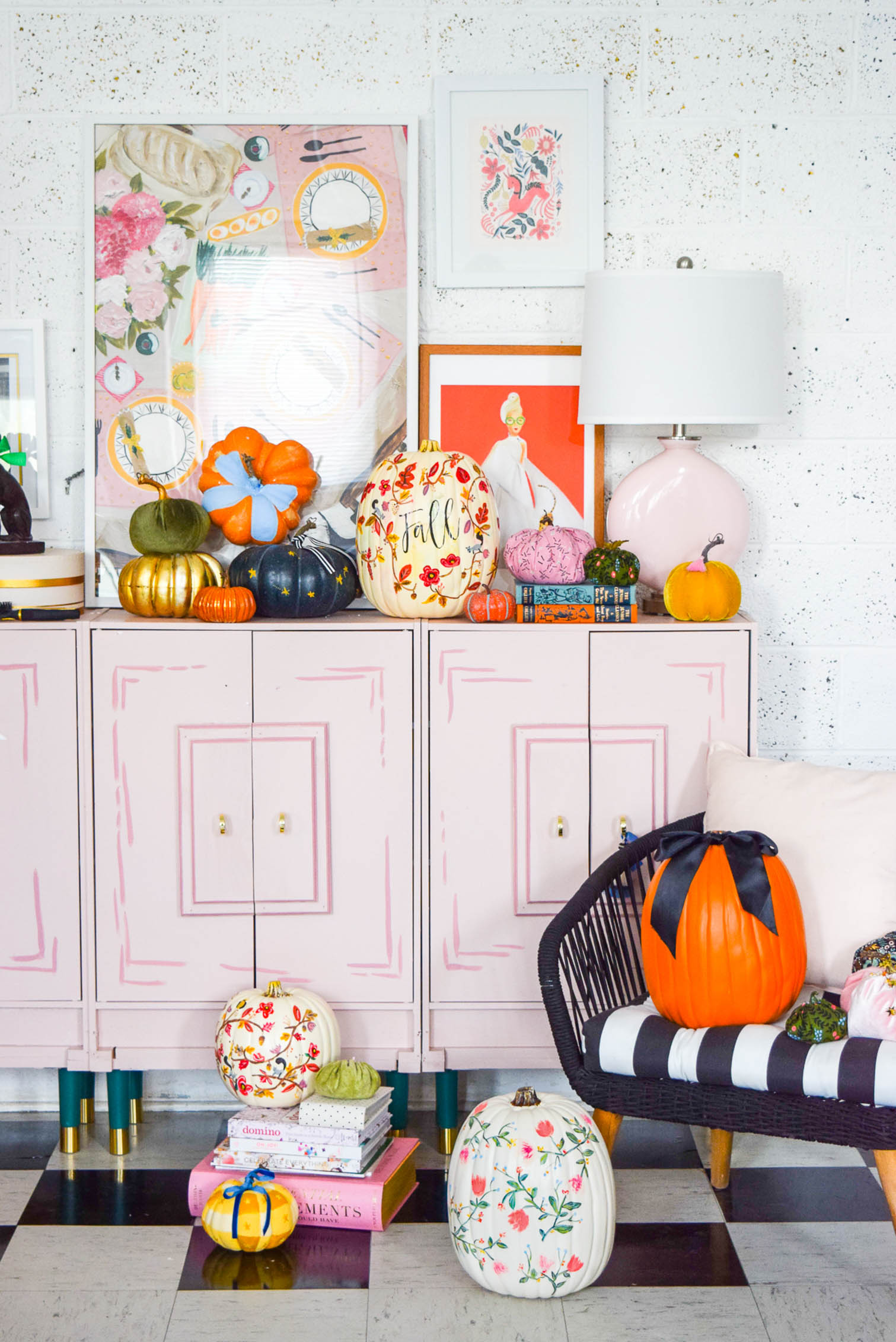 painted pumpkin display on a pink dresser with art