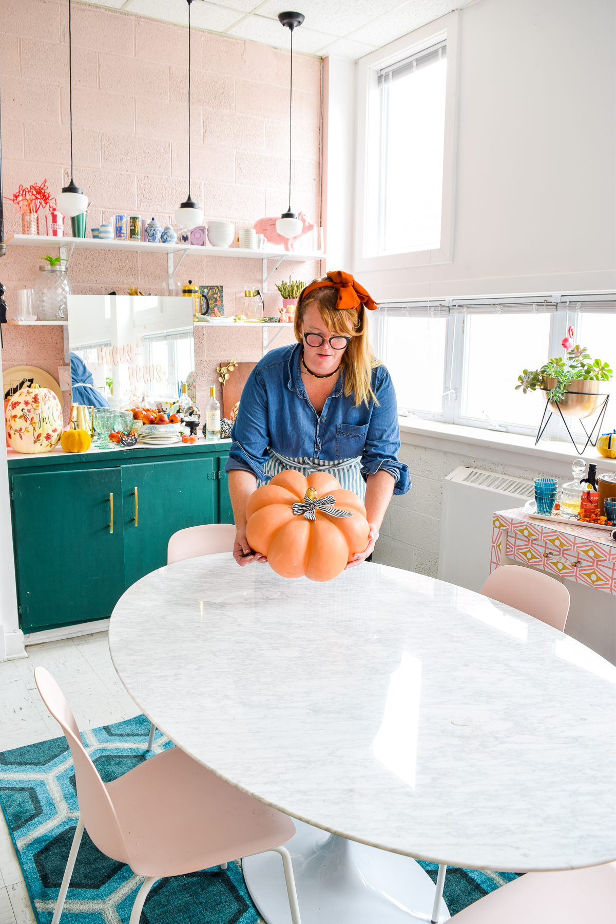 woman removing pumpkin from marble table