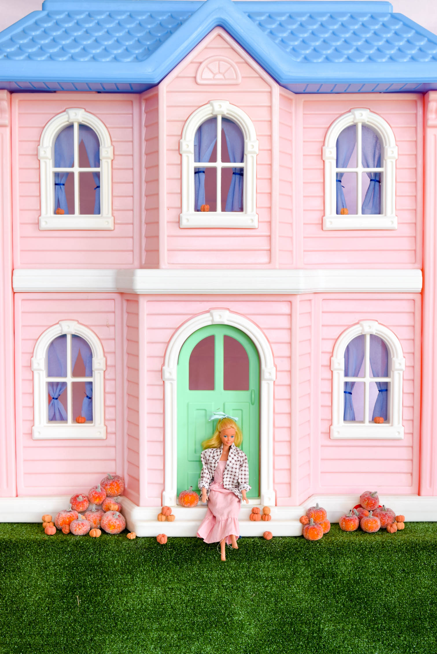 Barbie sitting on front step of large dream house with pumpkins o either side