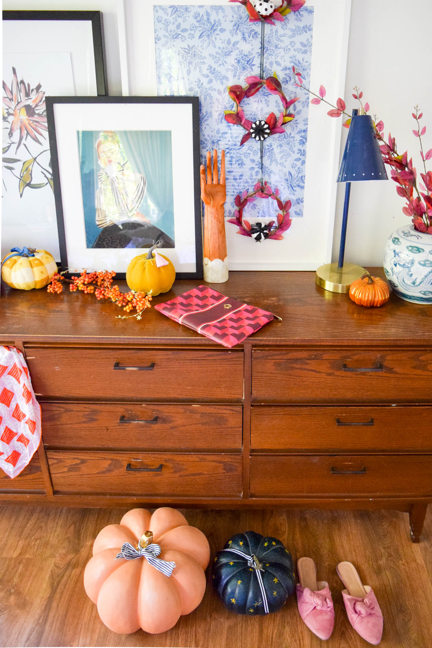 perspective shot of dresser with pumpkins and fall wreaths