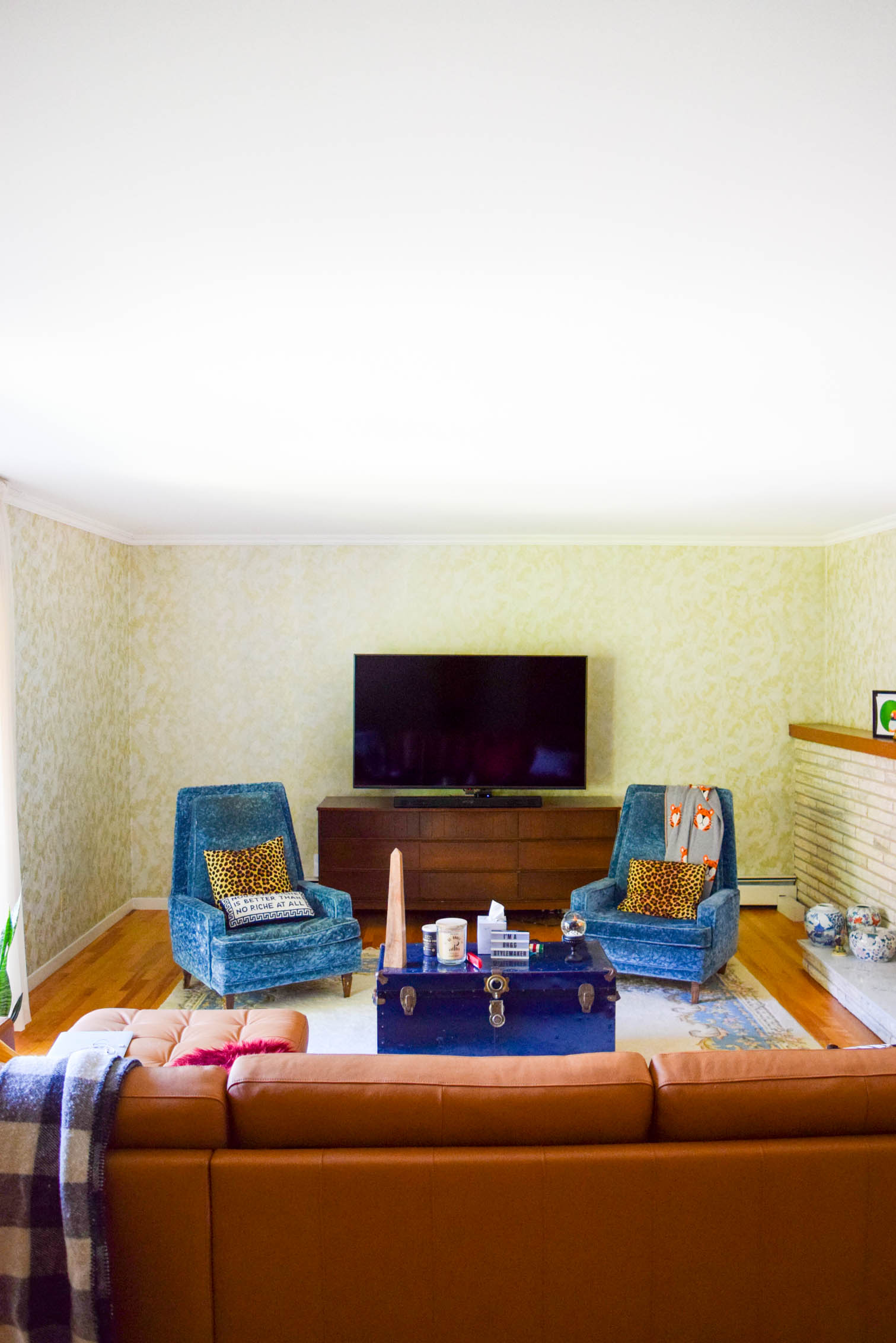 living room facing two blue chairs and a TV