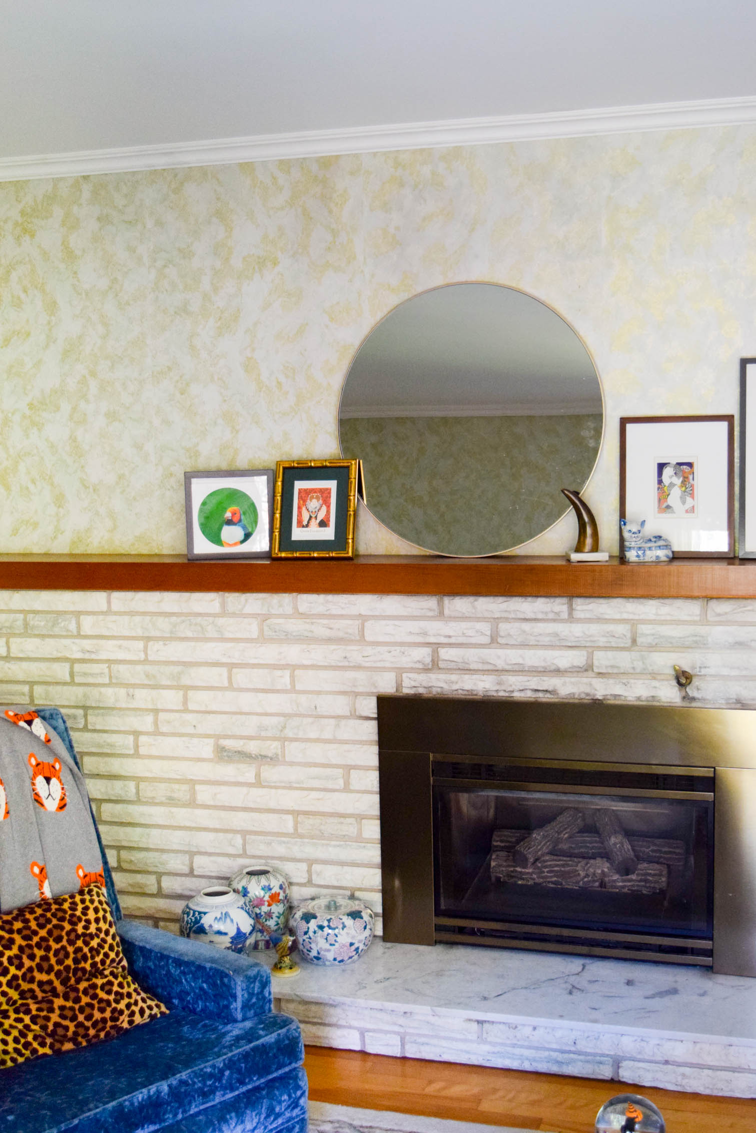 marble fireplace against tacky wallpaper