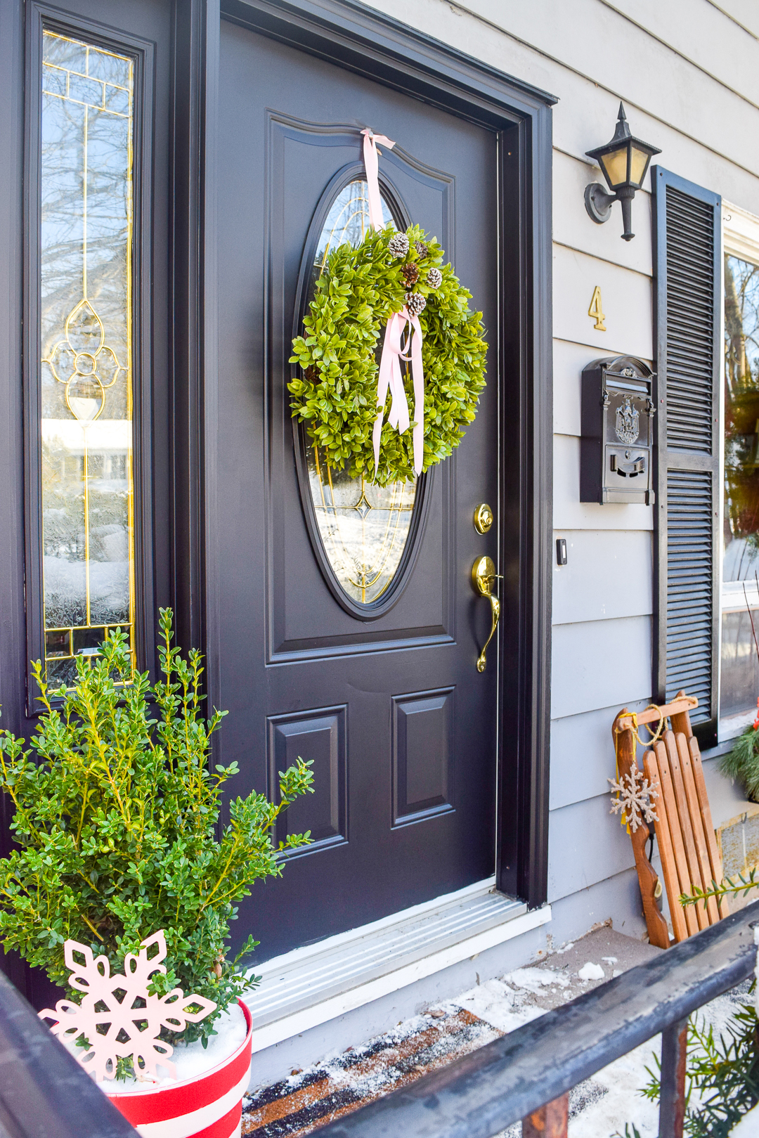 Give your home a classic & colourful holiday porch makeover with the help of Behr paint! Who doesn't need a sexy new black door, and colourful window baskets.