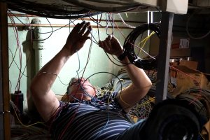 Don Philpott pulls wire from underneath the layout