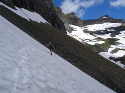 A hiker crosses a snowfield using trek poles