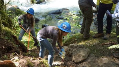 Rangers work to loosen large rocks to build a sill for the footbridge.