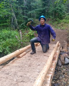 Crew member Steven pauses to celebrate before driving the last nail into some puncheon decking