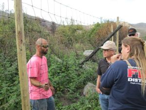A volunteer team discusses the repair of deer fencing in preparation for the winter.