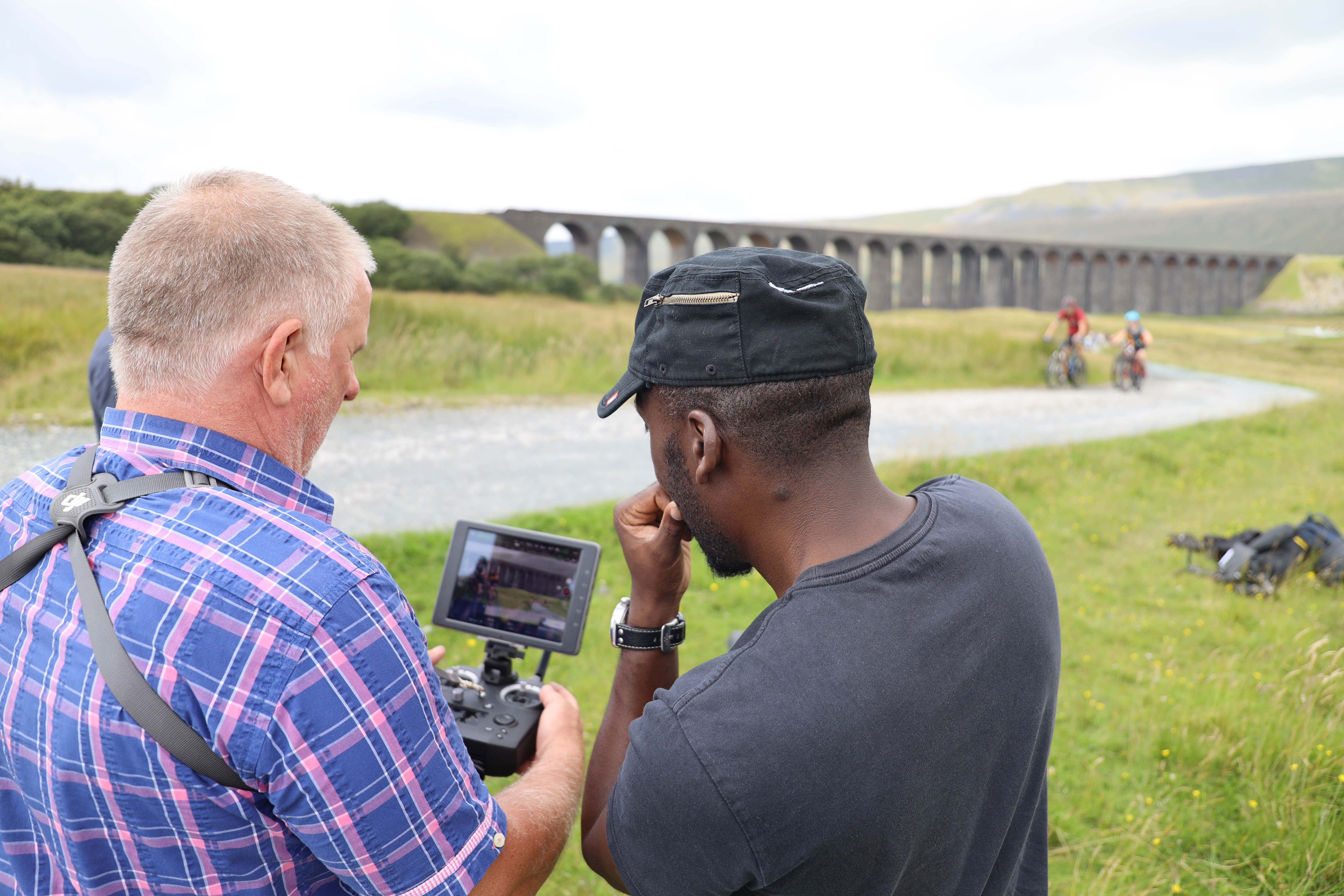Drone operator and director study shot of cyclists at Ribblehead viaduct for Cycle the Dales promotional video with Pocket Projects