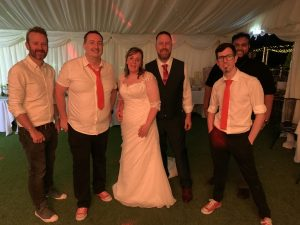 The Pocket Rockers pose with the bride and groom at their wedding at The Hampshire Hog