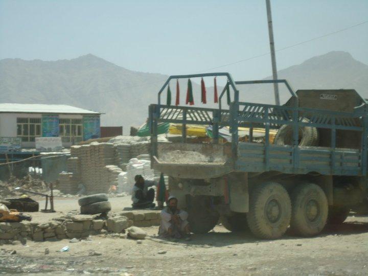 Man seeking shade under a truck (Company Road, near Arghandeh)