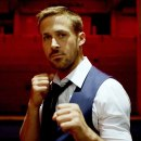 A film still from the movie Only God Forgives. It is an image of Ryan Gosling as Julian against a backdrop of a warehouse which is bathed in blood red light. Julian stands looking direct into the camera in white shirt, tie and waist coat with his fists up ready to fight.