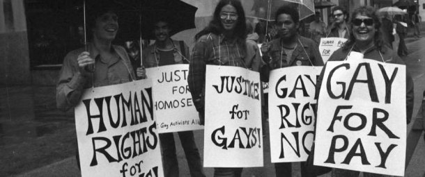 A black and white image of a LGBT Rights demonstration from the 1970s. One of the placards held by the five people pictured has been altered to say